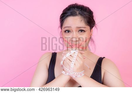 asian fat women , Fat girl , Chubby, overweight woman with measuring tapes around her mouth - Woman