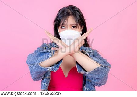 Asian girl wearing Face Mask show stop hands gesture for stop corona virus outbreak , protect spread