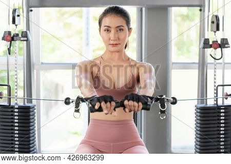 Close Up Fitness Slim Fit Woman In Sportswear Working Exercise With Machine In A Gym Fitness Room ,