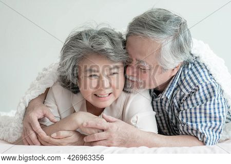 Happy love Elderly couple smiling , Senior couple old man and senior woman hugging in bed room - lif
