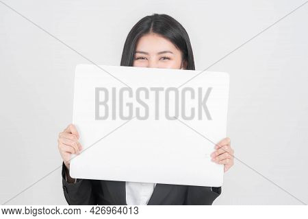 Portrait Young Working Woman In Black Suit Smiling And Holding A Blank Space For Advertising Banner