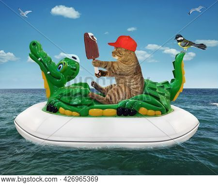 A Beige Cat In A Red Hat With Ice Cream Is Floating On An Inflatable Crocodile In The Sea At A Resor