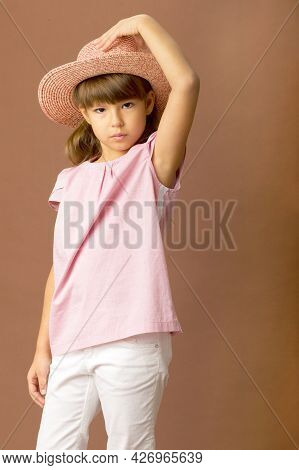 Adorable Girl Touching Her Straw Hat. Child In Pink T-shirt, White Pants And Straw Hat Posing On Bro