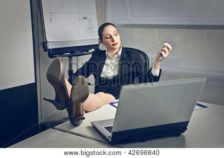 businesswoman talking on the phone with feet on the desk poster