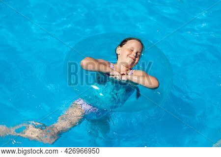 A Six-year-old Girl Enjoys A Swimming Pool, An Inflatable Circle, Summer And A Family Vacation