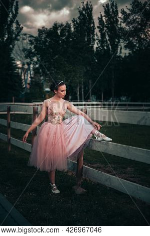 A Thin Ballerina Puts Her Foot On The Wooden Board Of The Horse Corral And Ties Ribbons On Pointe Sh