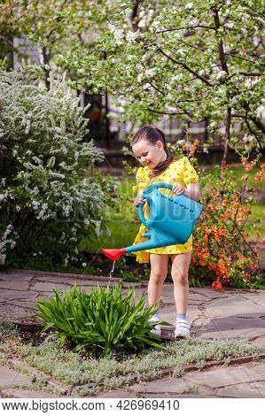 A Charming, Laughing Girl In Full Growth Waters Flowers From A Watering Can Outdoors, A Beautiful Bl