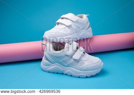 Side View Balance Of Two White Unisex Sneakers On A Pink Long Paper Roll On A Blue Background, One S