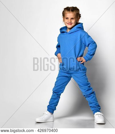 Little Girl In A Trendy Blue Tracksuit Having Fun On A White Background. A Child With An Emotional E