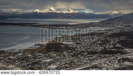 Panoramic Shot Of Ushuaia City At Afternoon And Andes Mountains At The Background With Sunlight And