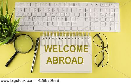 Welcome Abroad Text On Notebook With Keyboard On Yellow Background