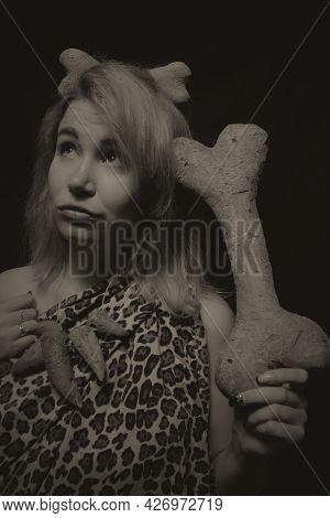 Prehistoric Woman Posing Over Dark Background With Huge Bone
