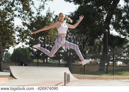 Healthy And Fit Atrractive Blonde Woman Leaping To The Right Over Obstacles At The Park While Lookin