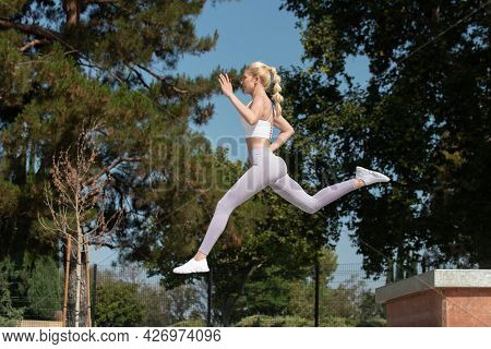 Healthy And Fit Atrractive Blonde Woman Leaping To The Left Over Obstacles At The Park While Looking