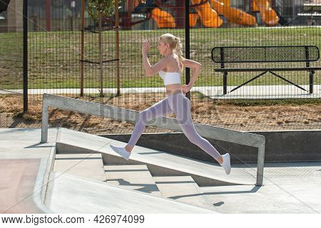 Healthy And Fit Atrractive Blonde Woman Leaping Up A Short Flight Of Concrete Stairs At The Park.