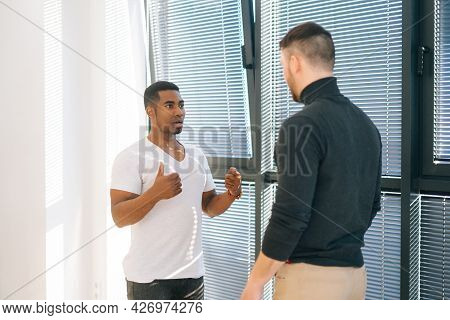 African American Male Office Worker Having Very Serious Conversation With Caucasian Colleague Standi