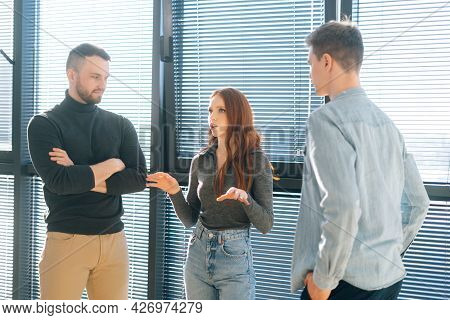 Front View Of Young Redhead Businesswoman Leader Having Conversation With Male Colleagues In Modern