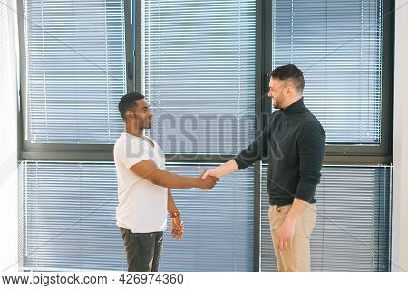 African American Manager Wearing Casual Clothes Shake Hand Of Man Client Or Customer Making Business