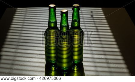 Three Green Glass Beer Bottles In The Shade Of The Blinds.