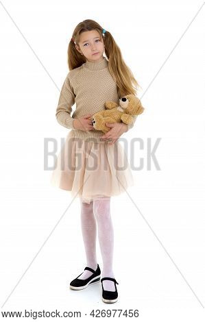 Preteen Girl Playing With Teddy Bear Toy. Beautiful Blonde Girl With Pigtails Wearing Knitted Jumper