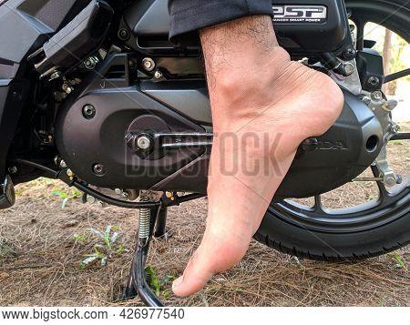 Malaysia, Kuala Terenganu 17 July 2021 : Feet Are Kicking The Motorcycle Starter