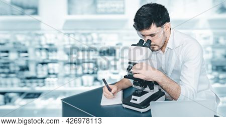 Male Research Medical Scientist Working With Microscope Testing Equipment In Laboratory, Professiona