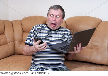 A Freak With A Surprised Face Holds A Laptop In His Hands While Sitting On Couch