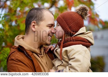 Family, Love And Happiness Concept - Cute Little Girl Kissing Her Father In Autumn Park
