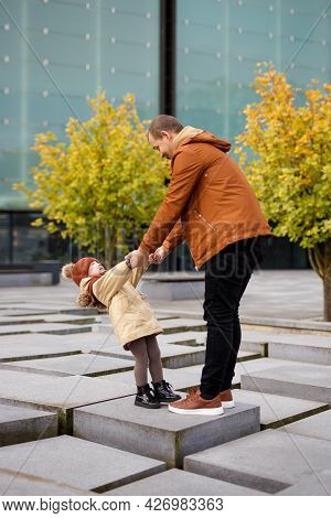 Family, Love And Happiness Concept - Happy Father And His Little Daughter Having Fun In Autumn Park