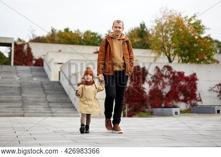 Family, Care And Happiness Concept - Happy Father And His Little Daughter Walking In Autumn Park