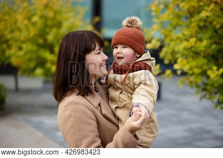 Family, Parenthood, Love And Happiness Concept - Smiling Mother And Her Little Daughter Walking In A