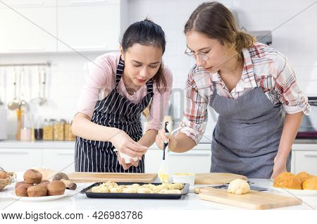 Girl Baking Cookies, Family Teenage Women Two Of Multi Ethnic Are Cooking Bread. Bakery In The Kitch