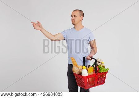 Young Man With Shopping Basket Full Of Products Taking Something Or Pointing At Something Over White