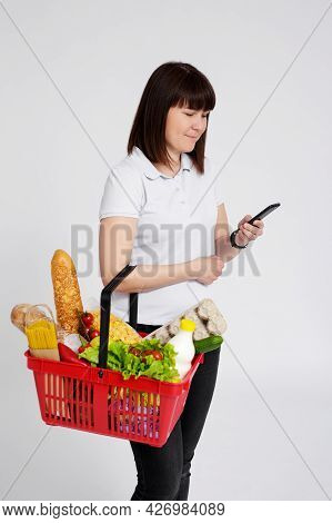Online Shopping Concept - Portrait Of Young Woman With Shopping Basket Full Of Products Using Smart