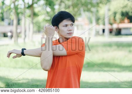 Young Asian Male Jogger Warming Up By Stretching Arms And Upper Body Before Running.