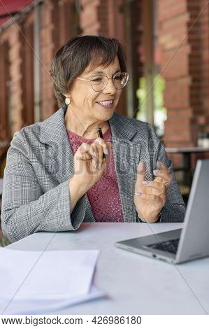 Smiley 60-years-old Woman Is Online Working In Front Of Laptop Monitor While Sitting In Summer Cafe.