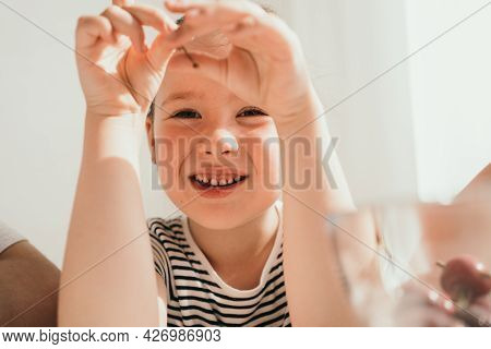 A Little Girl Eats Cherries. A Child On A Sunny Day In A Striped T-shirt. Close-up Portrait Of A Lit