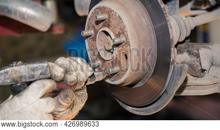 Gloved Hands Remove The Rear Rusted Wheel Hub. In The Garage, A Man Changes Parts On A Vehicle. Smal