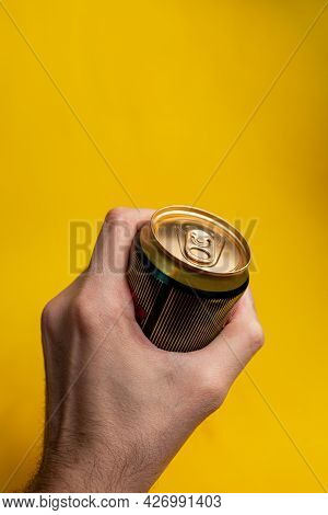 Tin Can In A Man's Hand On A Yellow Background.