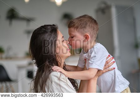 Little Boy Kiss His Mother Inside. Cute Baby Kissing Mom On The Nose.
