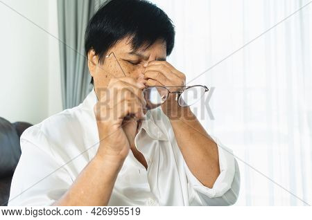 Tired Old Woman Removing Eyeglasses, Massaging Eyes After Reading Paper Book. Feeling Discomfort Bec