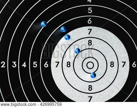 Balls Or Bullets For Pneumatic Shooting Lie On A Paper Target. Dark Inverted Illustration. Top-down