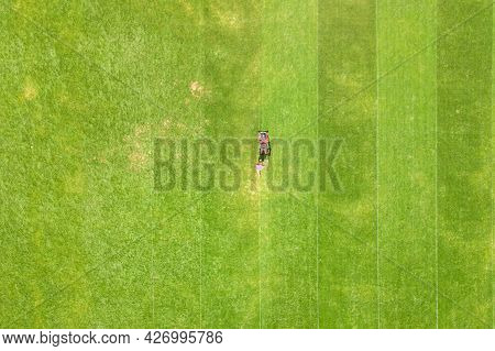 Aerial View Of Small Figure Of Man Worker Trimming Green Grass With Mowing Mashine On Football Stadi