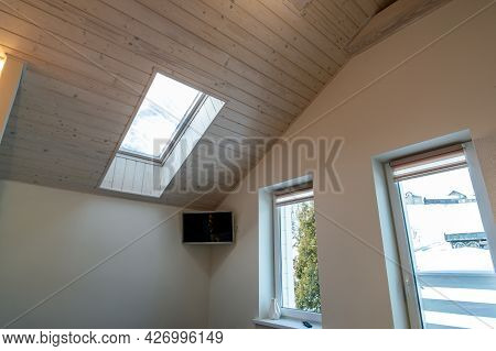 Wooden Ceiling In A Contemporary Mansard Room With Attic Window Of Decorative Planks Surface.