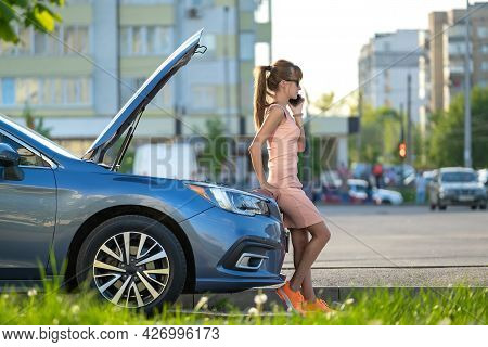 Helpless Woman Standing Near Her Car With Open Bonnet Calling Road Service For Help. Young Female Dr