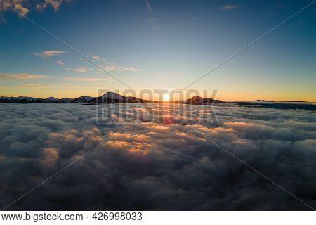 Aerial View Of Vibrant Sunrise Over White Dense Fog With Distant Dark Carpathian Mountains On Horizo