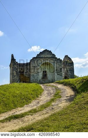 Ruins Of An Ancient Christian Temple On Background Of Blue Sky With Clouds. Road Leading Up To Old D