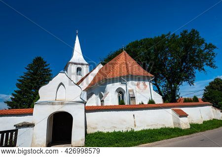 Misentea, Romania- 17 July 2021: Local Fortified Catholic Church Entrance N A Hot Summer Day.