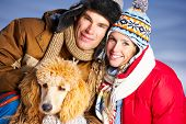 Young happy smiling couple with dog. Winter poster