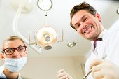 Scary dentist and assistant at a treatment, from the perspective of a patient